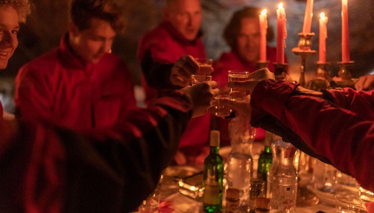 Eine Gruppe stösst beim Raclette in der Höhle mit Weisswein an.