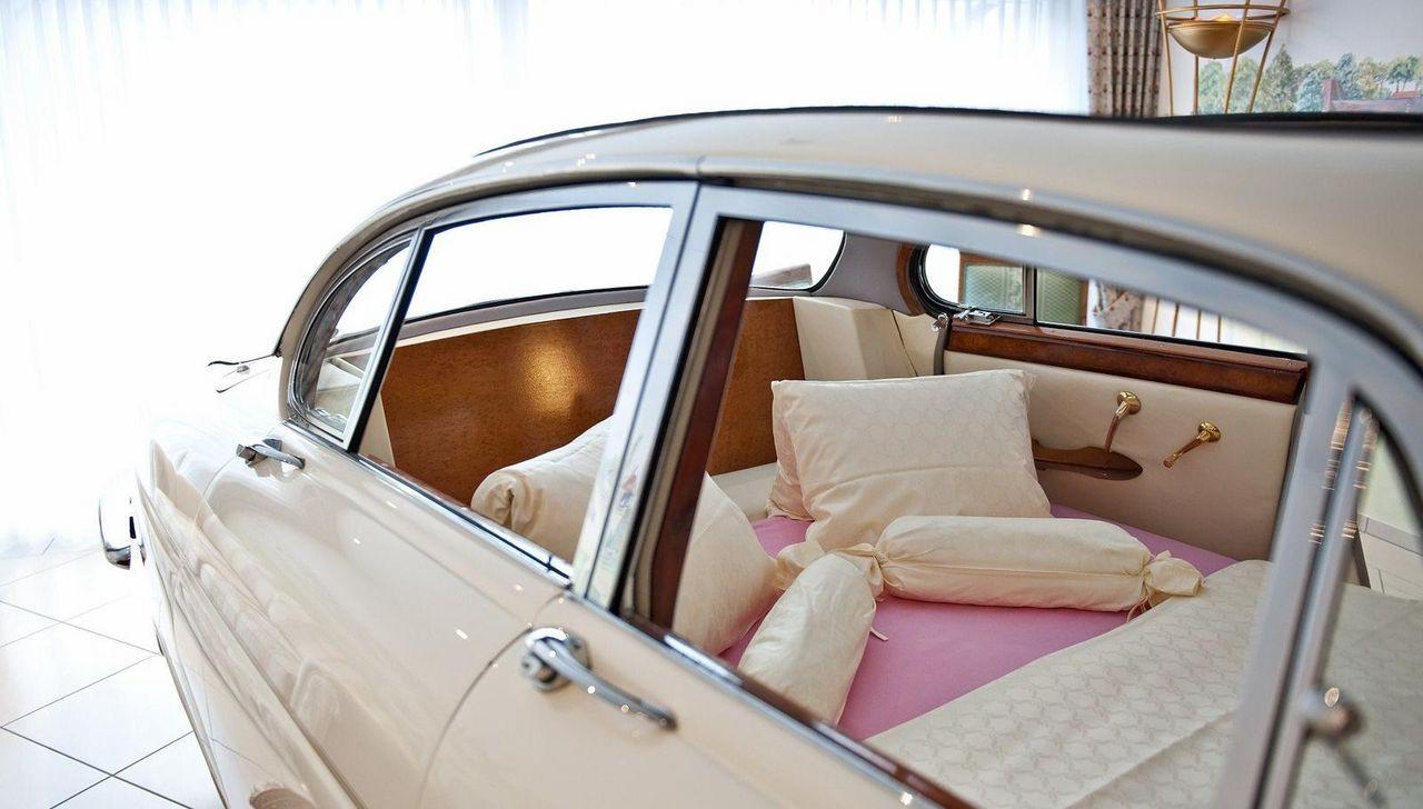 Blick durch das Autofenster auf das Bett in rosa und weiss.