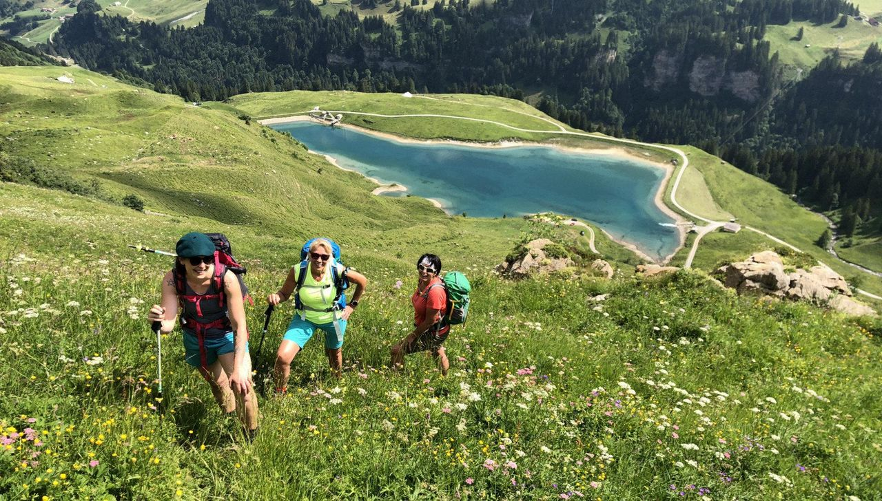 Drei Wanderinnen am Hang. Weiter unten liegt der Waldisee.
