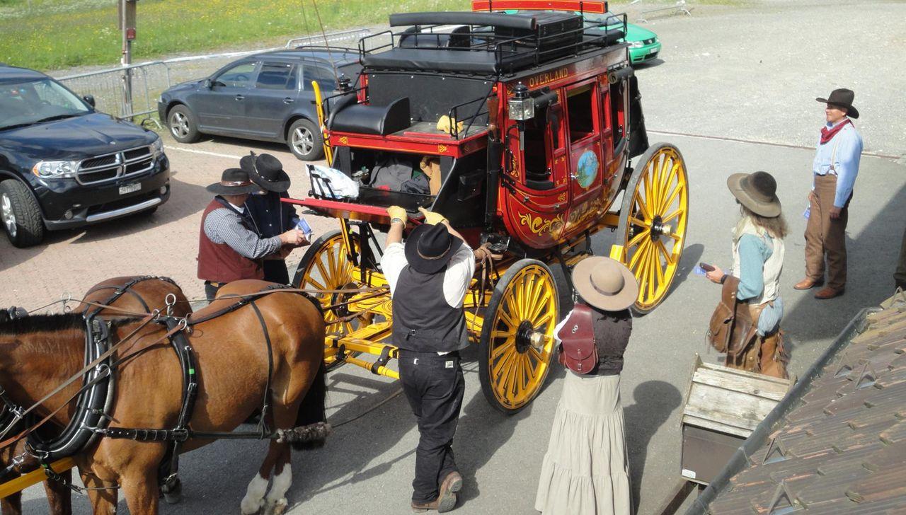 Um eine alte Pferdekutsche stehen Cowboys und Cowgirls mit Hut und allen Accessoires.