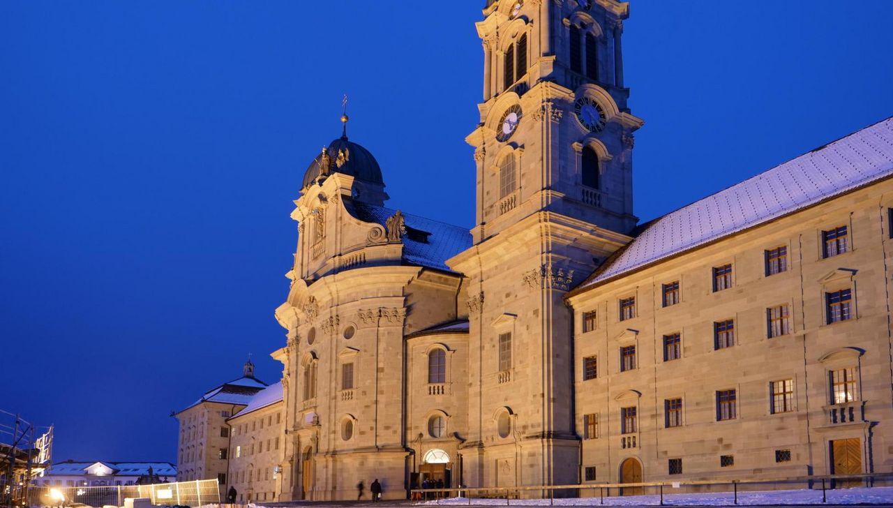 Die beleuchtete Front des Klosters Einsiedeln bei Nacht.