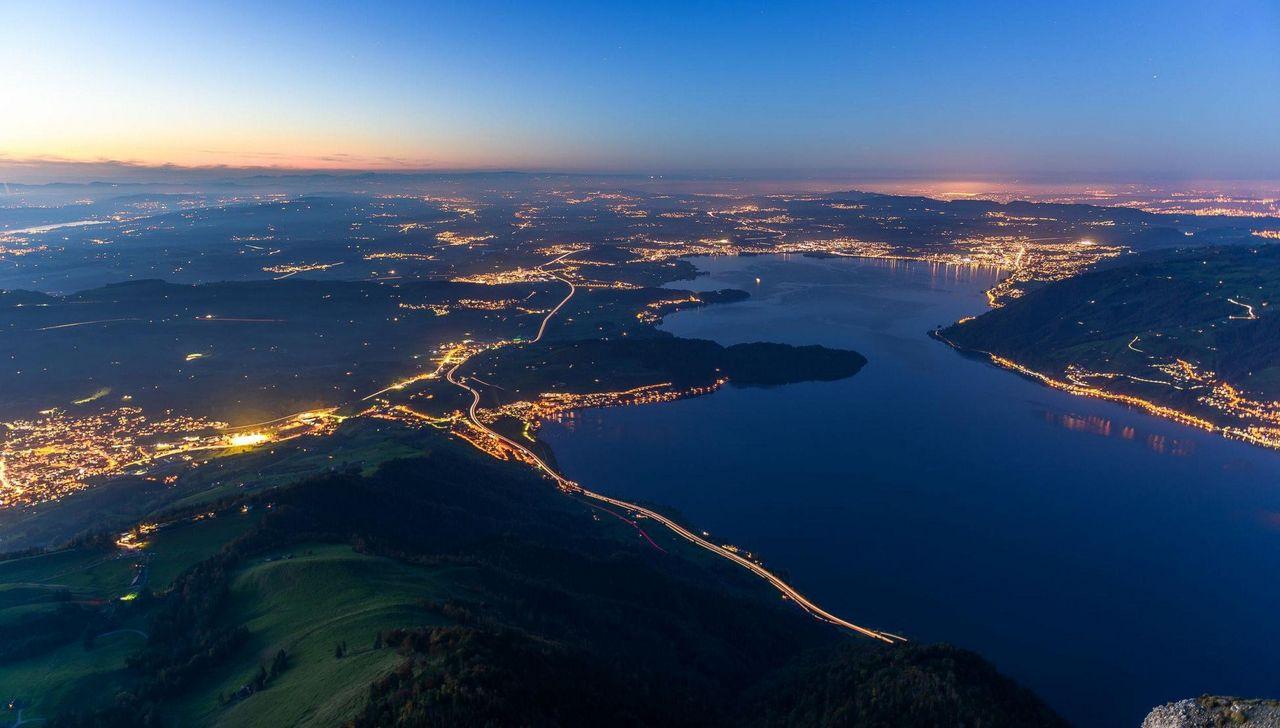 Die Aussicht von Rigi Kulm bei Nacht: dunkler see und viele Lichtpunkte.