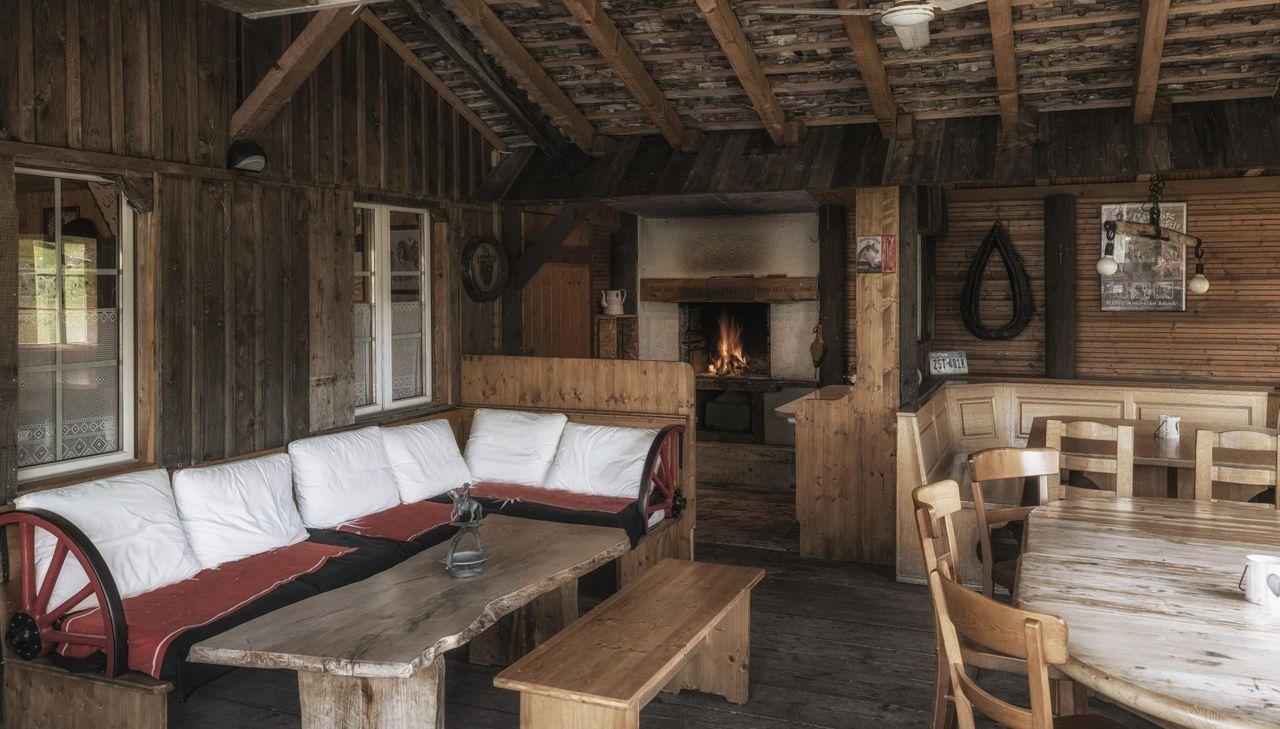 Die Sommerlounge mit Sofa und Kaminfeuer.