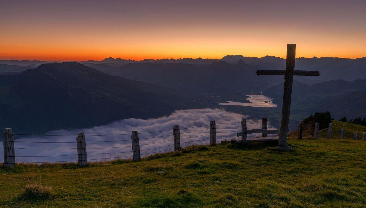 Ein Bergkreuz, das Nebelmeer mit Tal und die aufgehende Sonne.