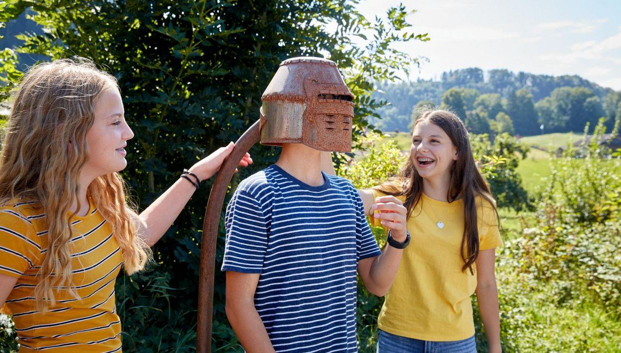 Schüler testen an einer Station des Morgartenpfads einen Helm.