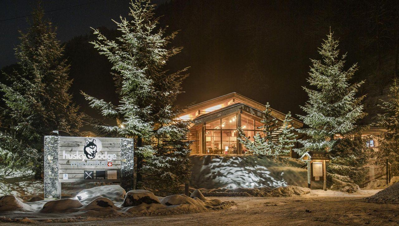 Aussenaufnahme des Restaurants im Winter mit verschneiten Tannen.